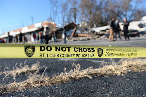 Police tape in front of smoldering remains of Prime Beauty Supply in Ferguson in the aftermath of riots. Photo taken on 11/25/14 by R. Gino Santa Maria / Shutterstock.com.