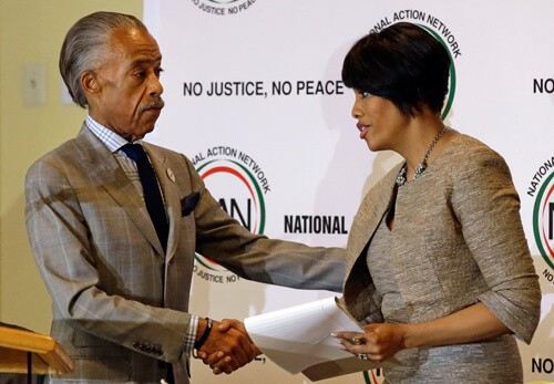 "NBC's Al Sharpton shakes hands with Baltimore Mayor Stephanie Rawlings-Blake as she prepares to speak at a summit to address issues surrounding the death of Freddie Gray and its aftermath at New Shiloh Baptist Church, Thursday, April 30, 2015, in Baltimore. Note the ""No Justice, No Peace"" slogan behind them. (AP Photo/Patrick Semansky)"